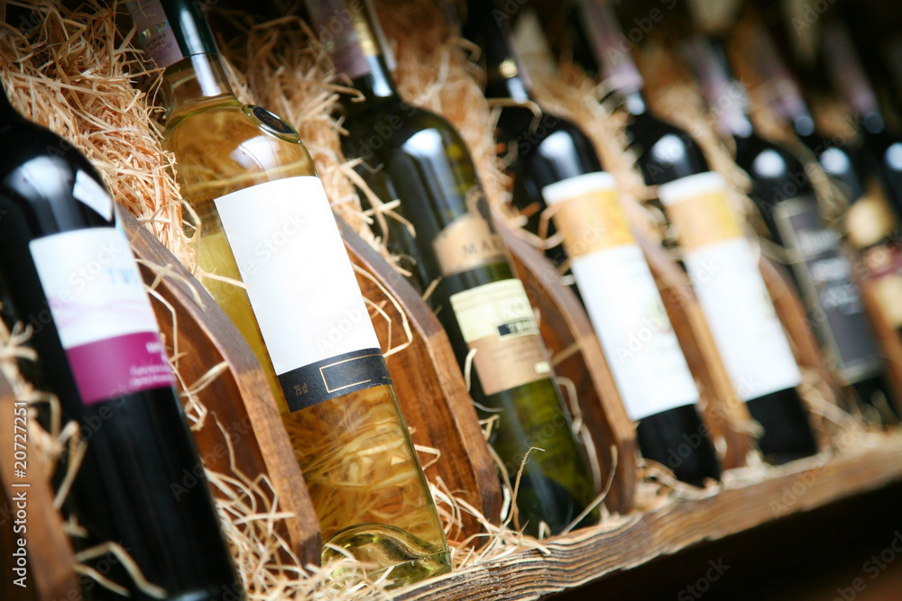 Closeup shot of wineshelf. Bottles lay over straw.