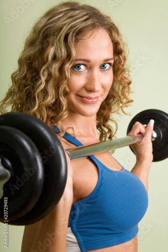 Foto op Plexiglas Fitness A young woman is engaged in weightlifting