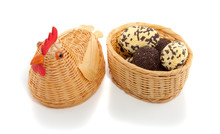 A Wicker Chicken And A Basket Of Chocolate Easter Eggs Isolated