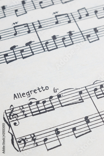 music notes sheet with selective focus on allegretto text Canvas Print