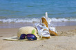 Sunglasses, Straw hat and sandal lay on sand at edge of sea