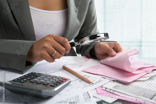 Businesswoman checking bills using magnifying glass Canvas Print