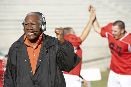 Photo football coach shouting and pumping fist on sideline