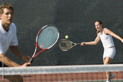mixed doubles player hitting tennis ball partner standing near net - 21308678