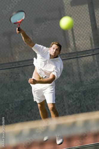 man serving tennis ball on tennis net - 21308699