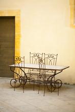 Chaises Et Tables En Fer Forgé Sur Fond De Pierre Jaune