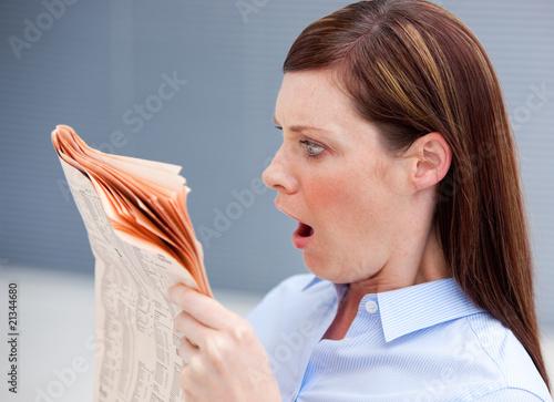Photo  Astonished businesswoman reading newspaper