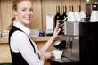 lächelnde kellnerin an der espressomaschine
