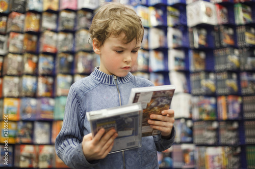 Fotografía  boy chooses one of two dvd in special store, ready contents