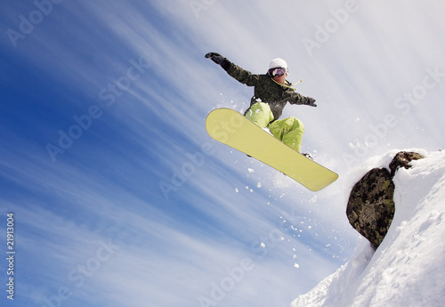 Fotografie, Tablou  Snowboarder jumping through air with  blue sky in background