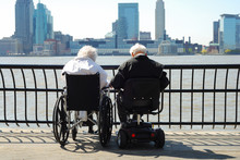 Senior Couple Sitting On A Wheelchair And A Scooter
