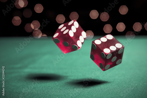 Photo  two dice rolling on table