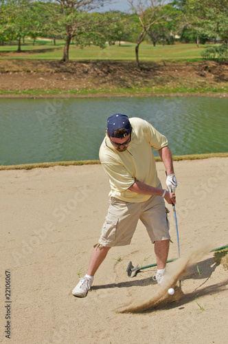 Photo Golfer hitting the golf ball out of a sand hazard.