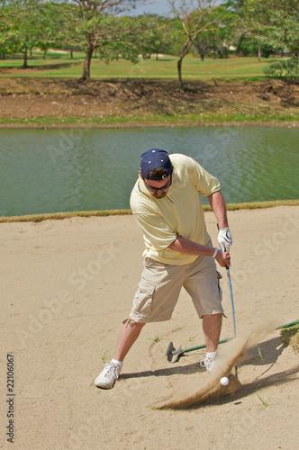 Golfer hitting the golf ball out of a sand hazard. Canvas Print