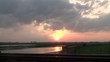 Sunset in the clouds next by a river and a highway – time lapse