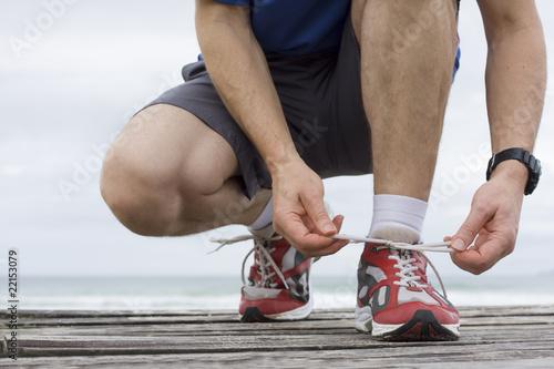 Foto  Läufer bindet seine Schuhe