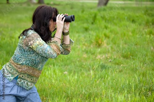 Valokuva  woman observing wildlife with binoculars