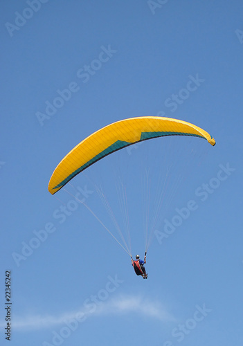 Foto op Canvas Luchtsport paraglider flying under beautiful blue sky