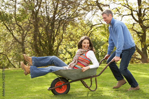 Couple With Man Giving Woman Ride In Wheelbarrow Poster Mural XXL