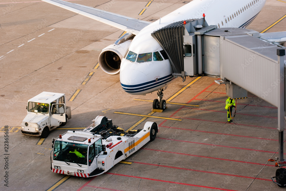 Fototapeta Airport. Airplane is being serviced by the ground crew.