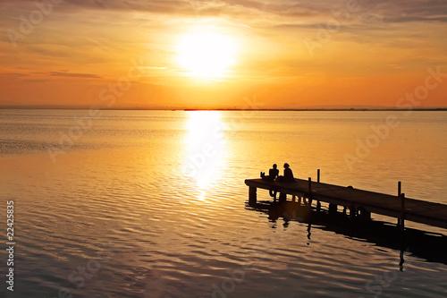 Tuinposter Pier mirando la puesta de sol