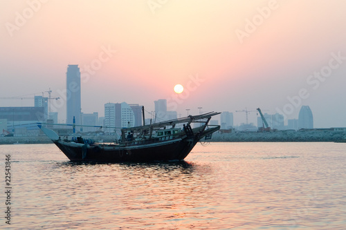 Fotografie, Obraz  Bahrain city silhouette and fishing dhow in sunset
