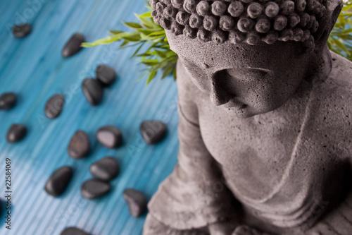 Foto op Plexiglas Boeddha Buddha mit Bambus, Massage Steinen und Schale mit Blüten