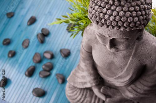 Foto op Aluminium Boeddha Buddha mit Bambus, Massage Steinen und Schale mit Blüten