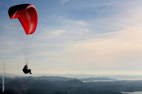 Fotobehang Luchtsport Paraglider flying over Norwegian coastal landscape