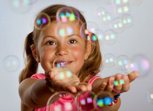 Pretty Young Girl Catching Bubbles That Are Floating In The Air
