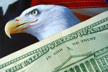 A Dollar Bill On The American Eagle Flag