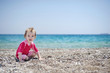 Cute toddler girl playing on a beach