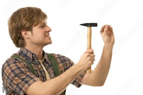 Obraz na plátně Young man hammering nail