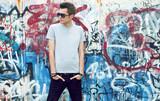 Fototapeta Młodzieżowe - young man posing in front of a colorful graffiti wall