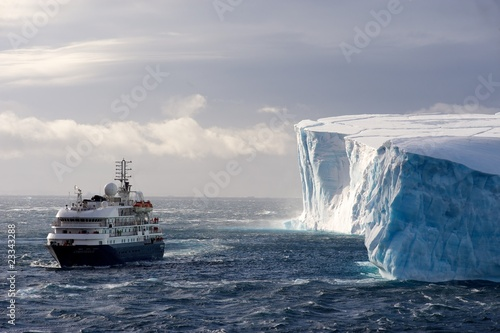 Foto op Canvas Antarctica The cruise ship Corinthian II in front of a huge Iceberg