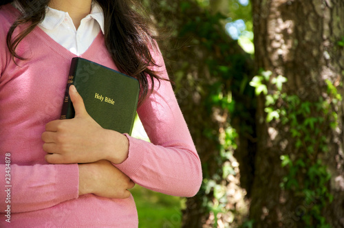 Cuadros en Lienzo Girl holding a Bible in nature