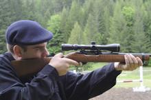 Man Looking Through Scope On A Rifle Gun