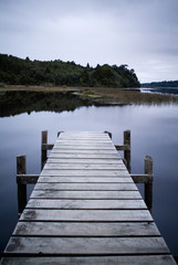 Obraz na SzkleWooden Jetty stretches out on glassy Lake Brunner in New Zealand