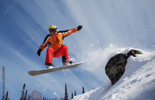 Fotografie, Obraz  Snowboarder jumping through air with  blue sky in background
