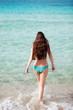 The beautiful girl in blue bikini costs in transparent sea water