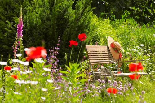 Obraz garden bench with straw hat within summer flowers 01 - fototapety do salonu