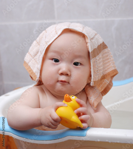 f4d18a490 Asian baby boy holding a yellow plastic duck in bath - Buy this ...