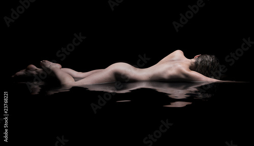 Fotografia  Nude woman lies in water, low key