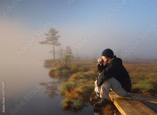 Stampa su Tela Hiker enjoying a morning coffee in a marsh