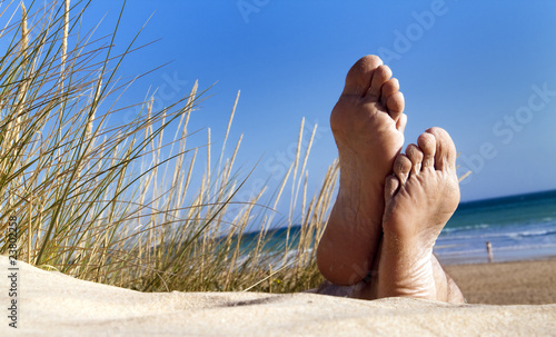Foto-Kissen - Men's feet lie relaxed in a dune on the beach (von spuno)