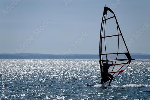 windsurfer silhouette against a sparking blue sea