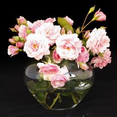Obraz na PlexiKleine, hellrosa Rosen in Vase vor schwarzem Hintergrund
