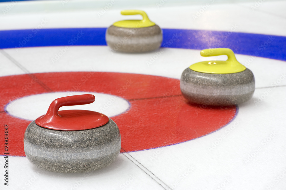 Fototapeta Group of curling rocks on ice