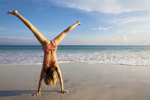 Woman In Bikini Doing Cart Wheel On Beach.