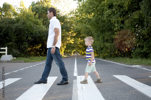 Leinwand Poster father with his son cross crosswalk